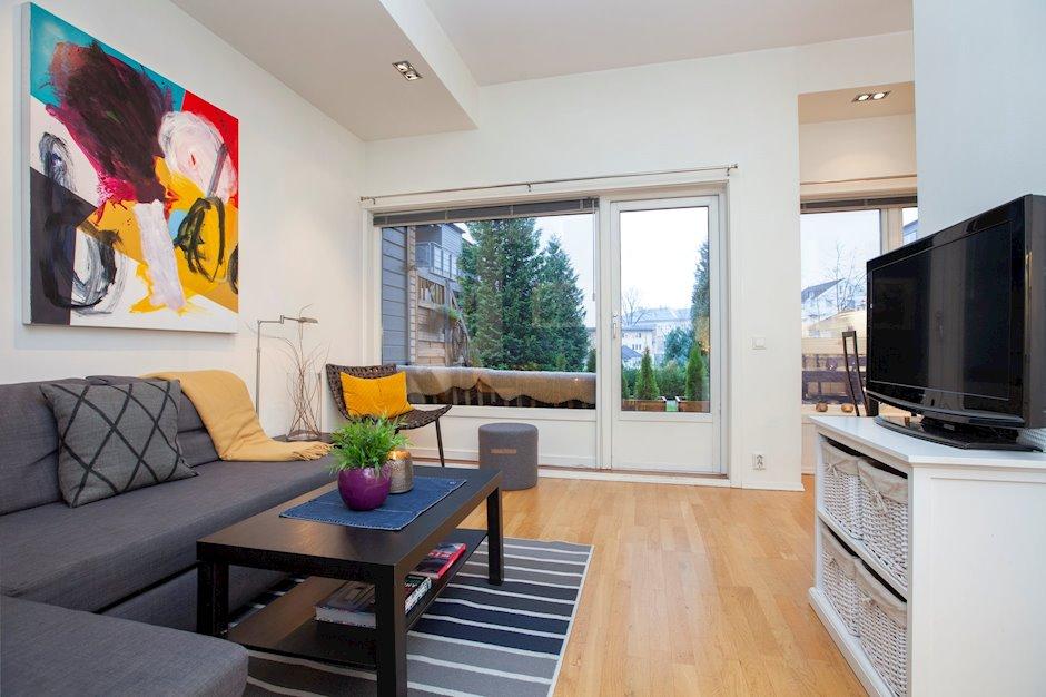 Lys og pen stue med parkettgulv og slette malte veggflater. Utgang til solrik sydvestvendt terrasse.