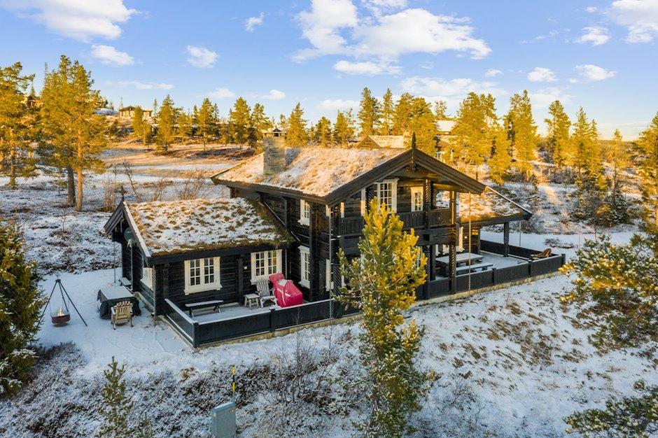 Stor skiferbelagt terrasse rundt hytta og koselig uteplass med bålpanne.